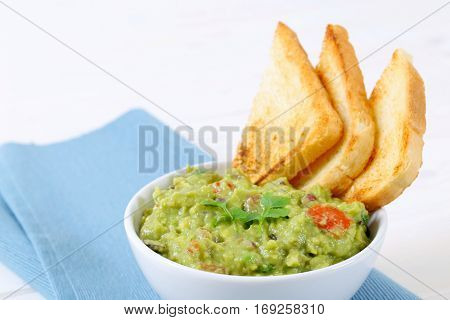 bowl of guacamole with toast bread on blue place mat - close up