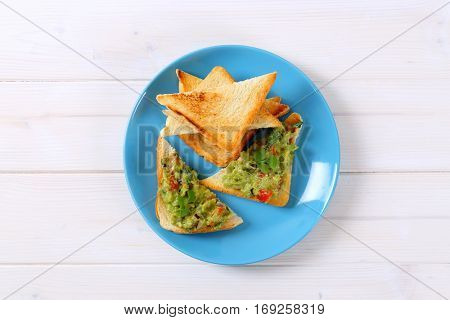 plate of toast bread with guacamole on white background