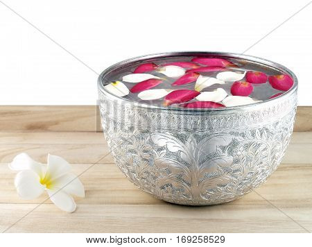 silver bowl with colorful flower petals floating on surface of water, used for decorative Asian style or in Songkran festival