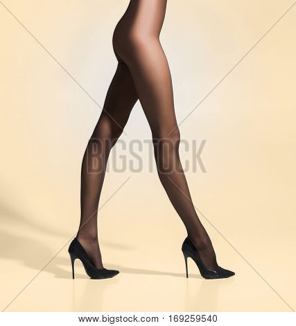 Fit and beautiful legs in sexy pantyhose. Woman in hosiery over beige background.