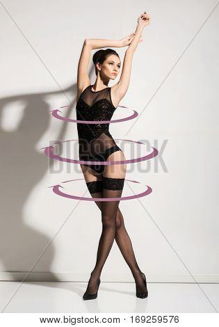 Young, sporty and seductive woman in stockings and sexy lingerie. Weight loss, perfect body, slim shape, nutrition, fitness, sport and diet concept.