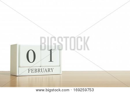 Closeup surface white wooden calendar with black 1 february word on blurred brown wood desk isolated on white background with copy space selective focus at the calendar