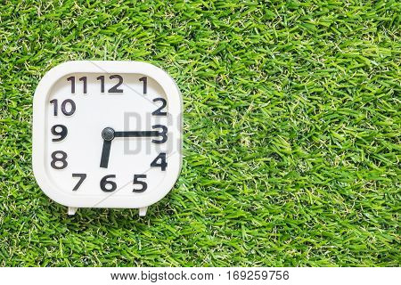 Closeup white clock for decorate show a quarter past six or 6:15 a.m. on green artificial grass floor textured background with copy space