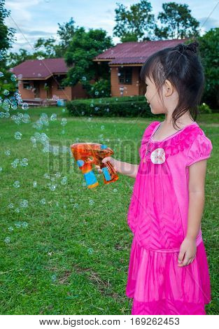 Asian Lovely Girl Playing On Green Grass At Yard.  Outdoor On Summer Day.
