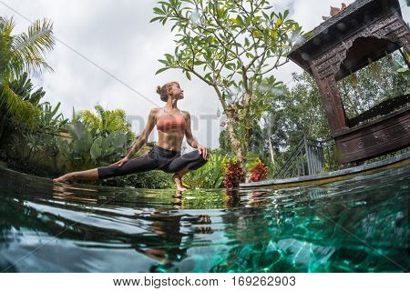 Young woman stretches and performs yoga in the green garden by the pool
