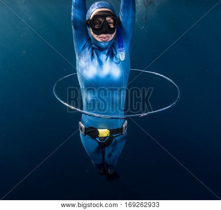 Woman free diver having fun with bubble ring