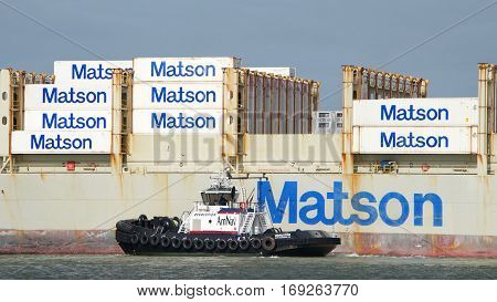 Oakland CA - January 20 2017: Tugboat REVOLUTION off the port side of Matson cargo ship KAUAI assisting the vessel to maneuver out of the Port of Oakland.