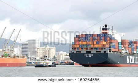 Oakland CA - January 20 2017: Tugboat MICHELLE SLOAN at the stern of cargo ship NYK THEMIS assisting the vessel to maneuver out of the Port of Oakland.