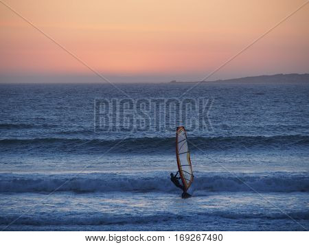 Ocean sunset, windsurfer silhouette sailing against a sunset background.