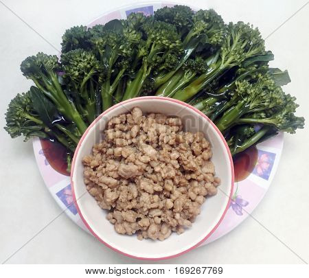 Fried minced pork served with broccoli vegetables filled with oyster sauce on the dish (Thai traditional food)