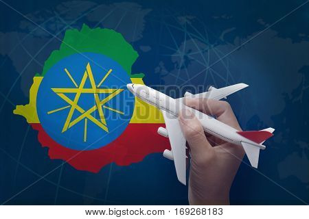hand holding airplane with map of Ethiopia.