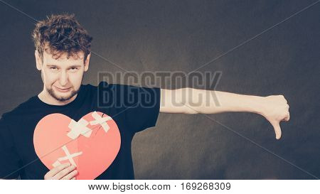 Heart broken concept. Unhappy sad man guy holding glued on love sign symbol. Human feeling repared by plaster. Valentines Day.