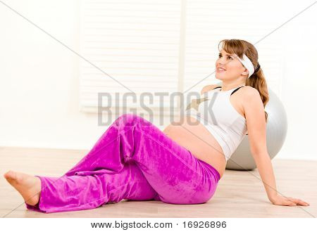 Smiling beautiful pregnant female making gymnastics at home