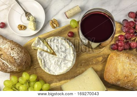 An overhead photo of a glass of red wine with cheese, white and rye bread, red and white grapes, and walnuts, at a wine pairing