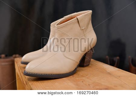 Shoes on the wooden shelf at the store. leather boots