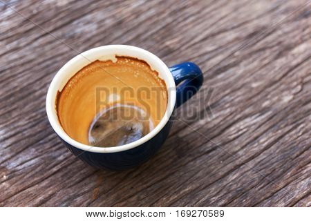 Empty cup of coffee with coffee espresso foam on olden wooden background
