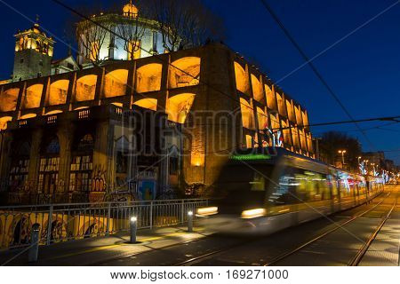 PORTO, PORTUGAL - JAN 6, 2017: Train of Porto Metro on Dom Luis iron Bridge in Old Town at night. The network has 6 lines and reaches seven municipalities within the metropolitan Porto area.