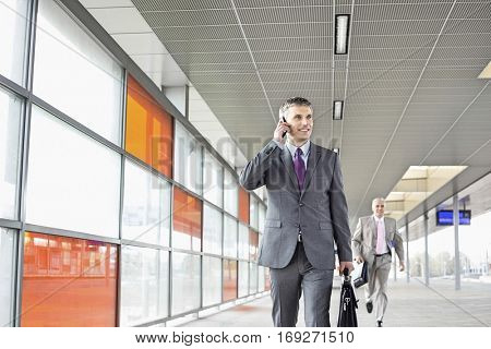 Middle aged businessman on call while walking in railroad station