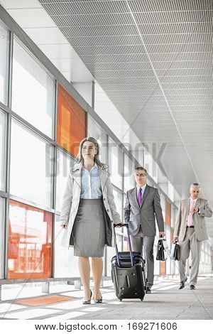 Full length of businesspeople with luggage walking in railroad station