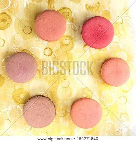 A photo of vibrant macarons, shot from above on a bright yellow background texture, forming a frame for copy space