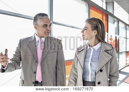 Businessman communicating with female colleague while walking in railroad station