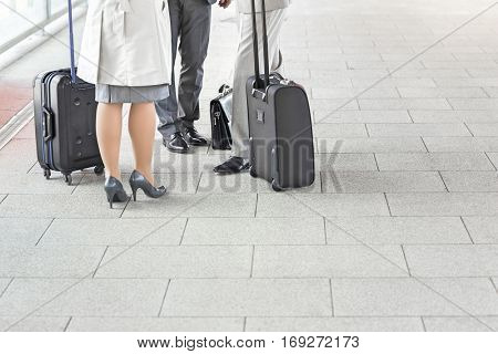Low section of businesspeople with luggage standing on railroad platform
