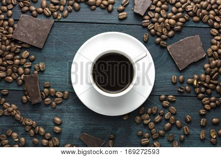 A cup of black coffee, shot from above on a wooden boards texture, with beans and chocolate pieces scattered around. Selective focus