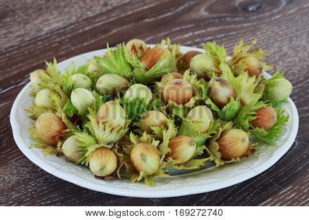 handful of hazelnuts in the plate on a wooden table