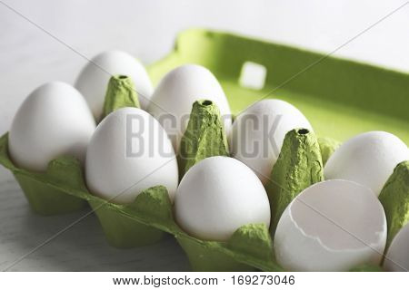 Raw eggs in package on wooden table