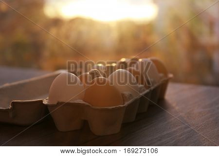 Raw eggs in package on kitchen table