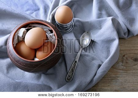 Raw eggs in bowl on kitchen table