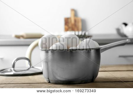 Raw eggs in saucepan on kitchen table