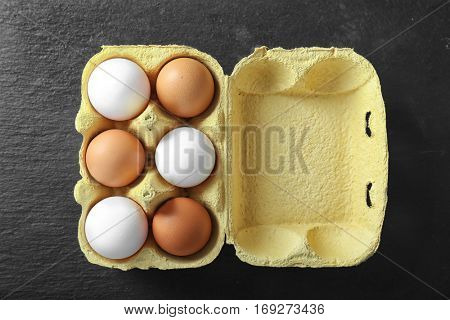 Raw eggs in package on black background