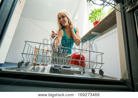 young woman removing dishes from the dishwasher