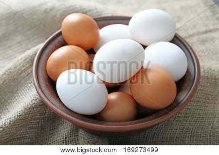 Bowl with raw eggs on fabric background