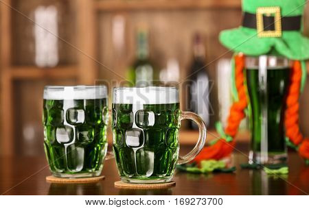 St. Patrick Day concept. Glasses of green beer on bar counter and blurred background