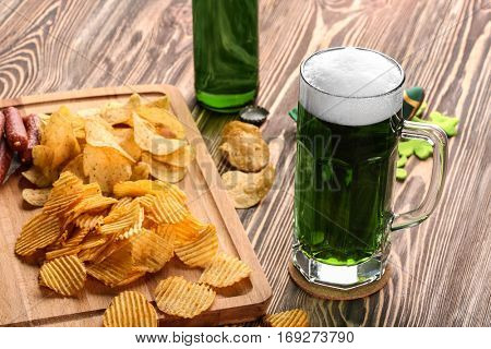 St. Patrick Day concept. Glass of green beer with crisps and sausages on wooden board, closeup