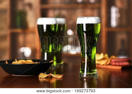 St. Patrick Day concept. Glasses of green beer and crisps on bar counter and blurred background