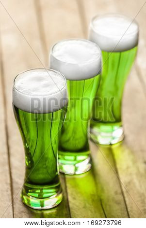 St. Patrick Day concept. Glasses of green beer in a row on wooden background, closeup