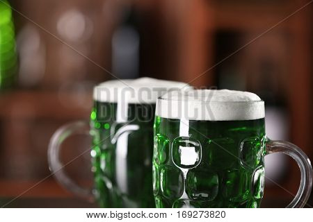 St. Patrick Day concept. Glasses of green beer on blurred background, closeup