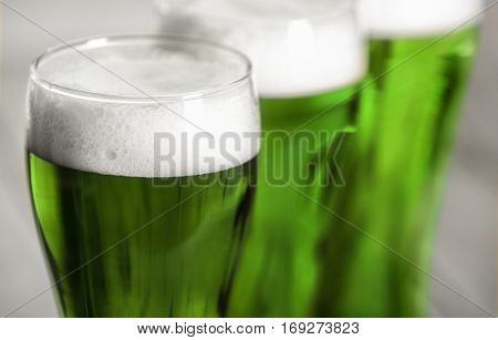 St. Patrick Day concept. Glasses of green beer in a row, closeup