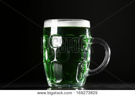 St. Patrick Day concept. Glass of green beer on black background