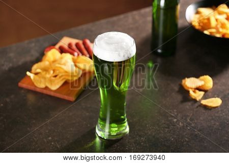St. Patrick Day concept. Glass of green beer and board with crisps and sausages on grey table