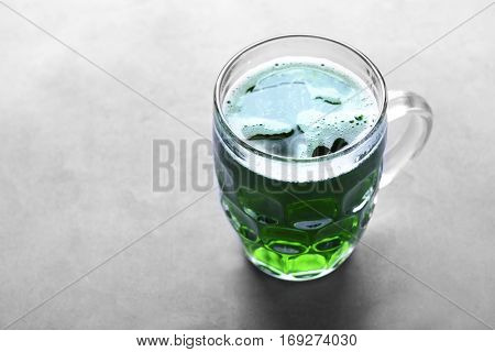 St. Patrick Day concept. Glass of green beer on grey table