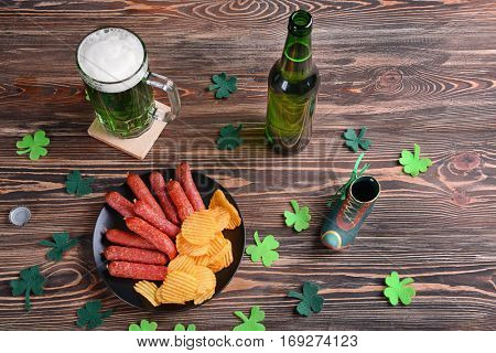 St. Patrick Day concept. Glass of green beer and plate with crisps and sausages on wooden table