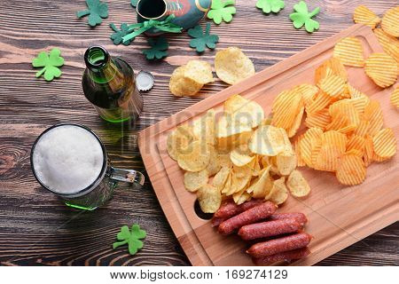 St. Patrick Day concept. Glass of green beer with crisps and sausages on wooden board