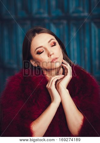 Fashion model Girl in red fur coat. Beautiful luxury winter woman. Fashion model girl portrait with closed eyes