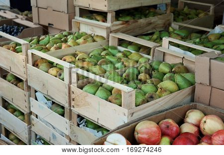 Wooden crates with juicy pears on market