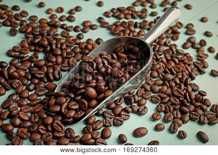 Roasted coffee beans and metal scoop on wooden table closeup