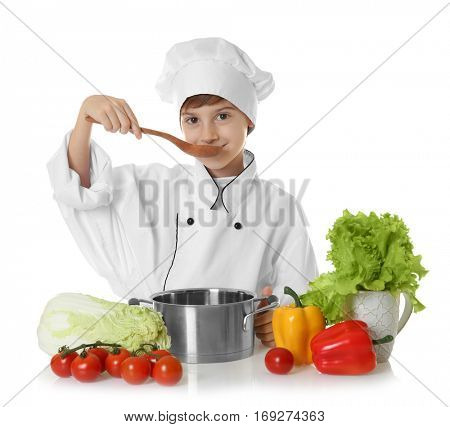 Cute boy in chef uniform preparing tasty soup, on white background